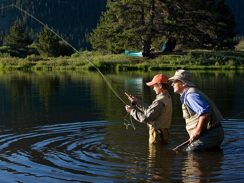 man teaching boy to fish