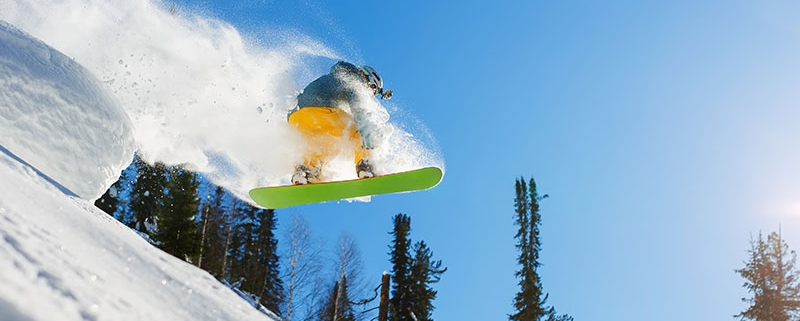 Snowboarder in the air off a jump with snow trailing behind him.