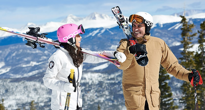 A couple carrying their skis on the mountain smiling and laughing