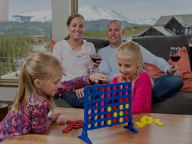 Kids playing Connect 4 while Parents watch